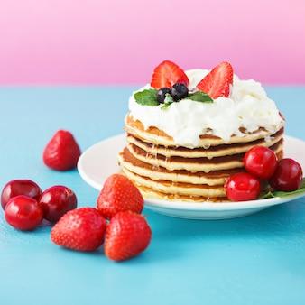Panquecas em um prato com chantilly, mel, morangos, hortelã e cerejas sobre um fundo azul e rosa brilhante.