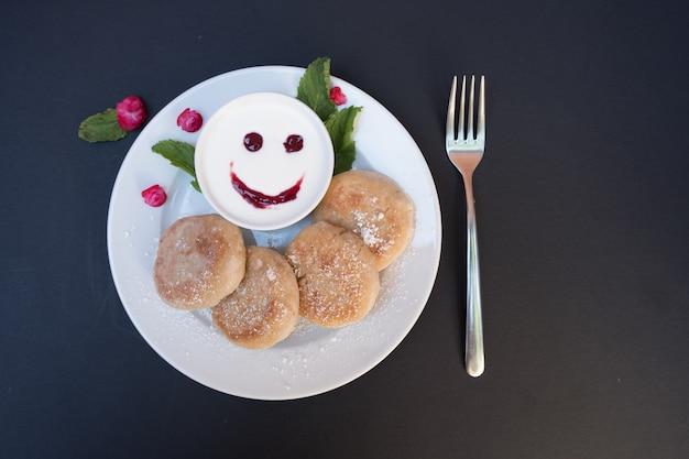 Panquecas em um prato com creme de leite em um fundo preto. café da manhã alegre com um sorriso.