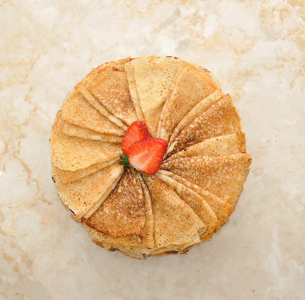 Panquecas em um prato com morangos em uma superfície de mármore