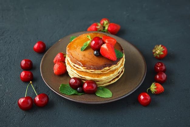 Panquecas em um prato com morangos, hortelã, mel e cereja em um fundo preto escuro.
