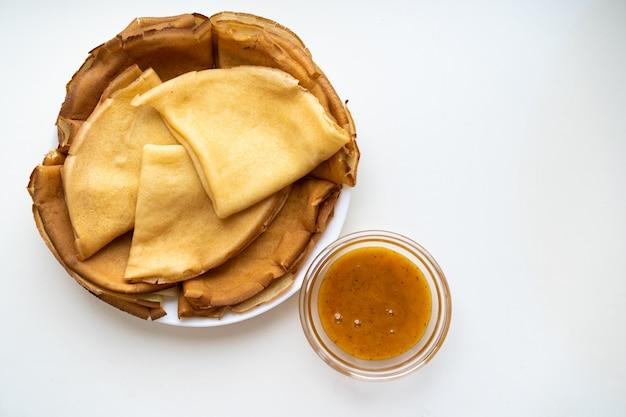 Panquecas em um prato estão sobre uma mesa branca, ao lado de uma tigela pequena de mel, o feriado tradicional de maslenitsa, semana da panqueca