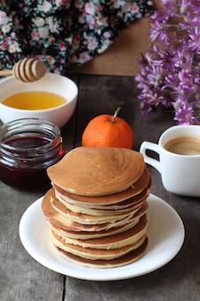 Panquecas em um prato sobre uma mesa de madeira com mel