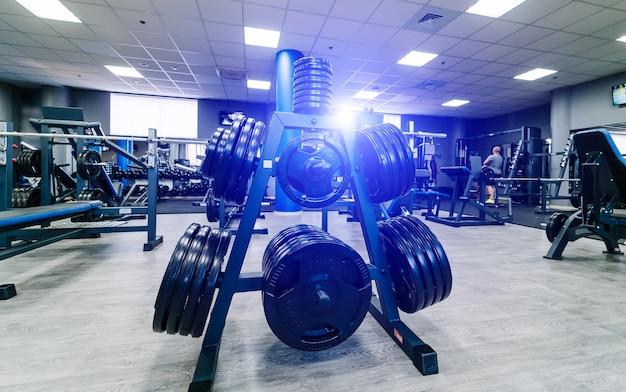 Panquecas enormes para um haltere em uma academia. esporte e conceito de vida saudável. conjunto de panquecas no fundo do ginásio. closeup de equipamento de esporte.