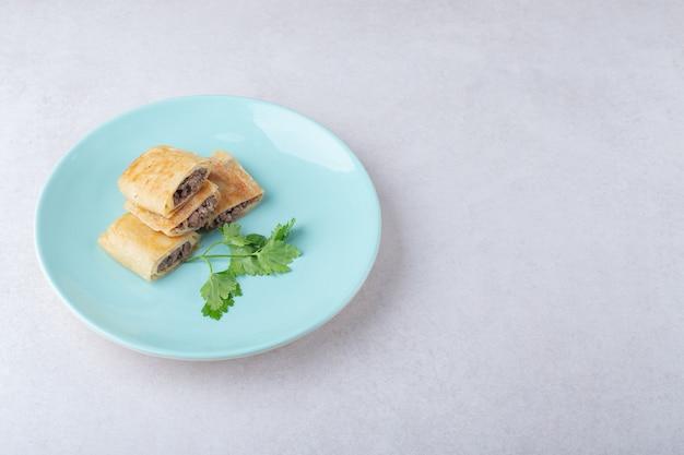 Panquecas fatiadas com carne no prato, no mármore.