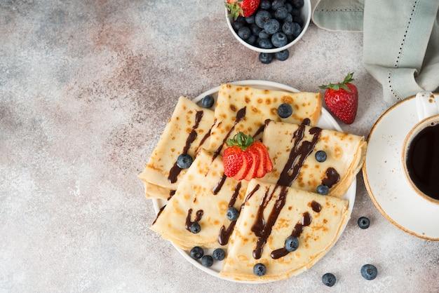 Panquecas finas caseiras com frutas e chocolate, vista de cima