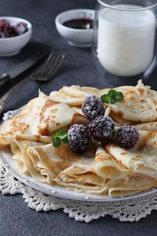 Panquecas finas com farinha de trigo, ovos e kefir, servidas com amoras, geleia e um copo de leite na mesa cinza escuro