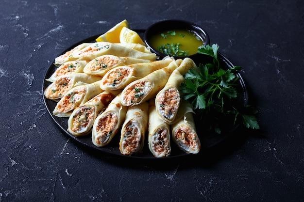 Panquecas finas com recheio de cream cheese, salmão e salsa, servidas em um prato preto sobre um fundo escuro de concreto