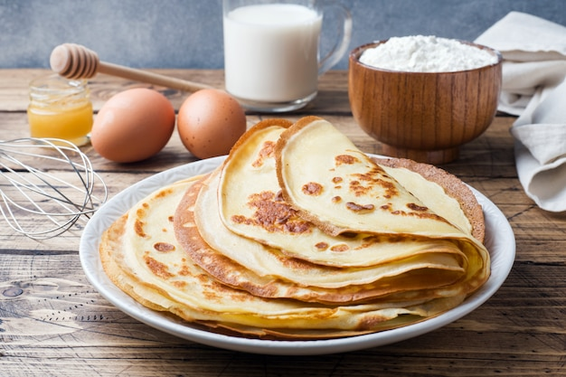 Panquecas finas em um prato. fundo de madeira ingredientes para cozinhar ovos, leite, farinha.