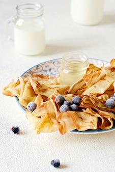 Panquecas fininhas caseiras com frutas, mel e leite no café da manhã.