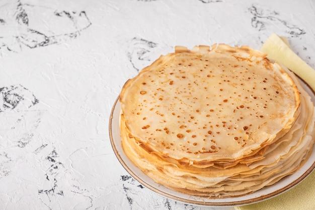 Panquecas fininhas caseiras em um prato. copie o espaço
