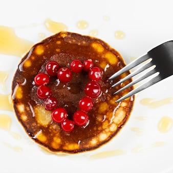 Panquecas fritas com coração de cranberry em forma de mel em um prato, isolado.