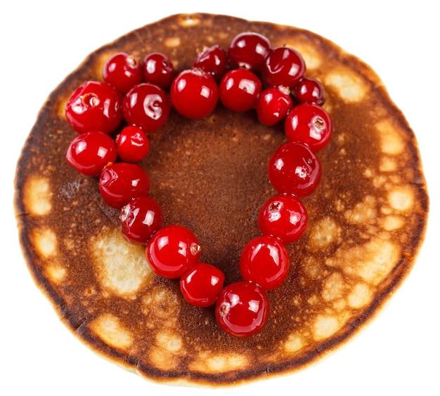 Panquecas fritas com cranberries em forma de coração isoladas no fundo branco.