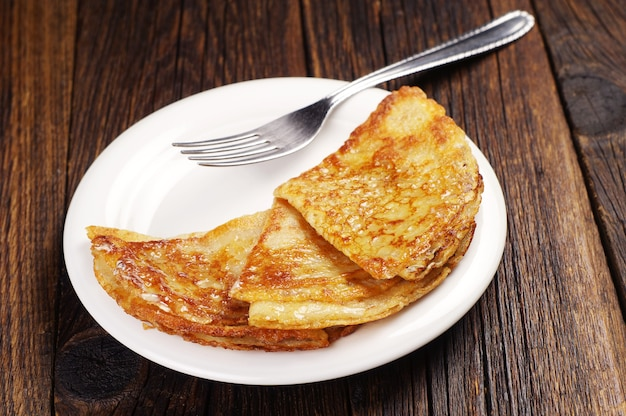 Panquecas fritas com manteiga em um prato branco na velha mesa de madeira