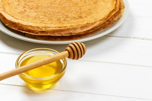 Panquecas fritas com mel na velha mesa de madeira. vista do topo