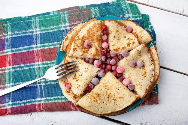 Panquecas fritas russas com cranberry na velha mesa de madeira. vista do topo. postura plana. forma de estrela