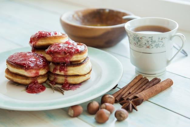Panquecas, geléia, mel, canela e uma xícara de café na mesa