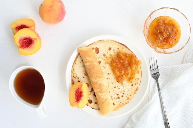 Panquecas grandes com geléia, chá e pêssegos em fundo branco.