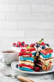Panquecas listradas brancas azuis vermelhas caseiras com chantilly fresco, amora e mel, superfície de pedra cinza claro de manhã