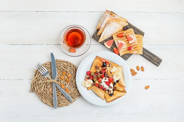 Panquecas na tábua de madeira com chá, amêndoas, faca, garfo, uvas e framboesas