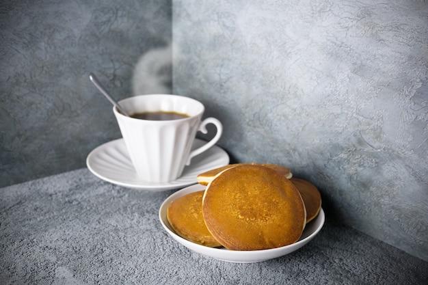 Panquecas no prato e café com vapor em xícara de porcelana na superfície cinza, talheres brancos com pastéis e bebida quente.