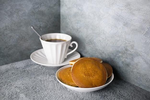 Panquecas no prato e café em xícara de porcelana na superfície cinza, talheres brancos com pastéis e bebida quente.