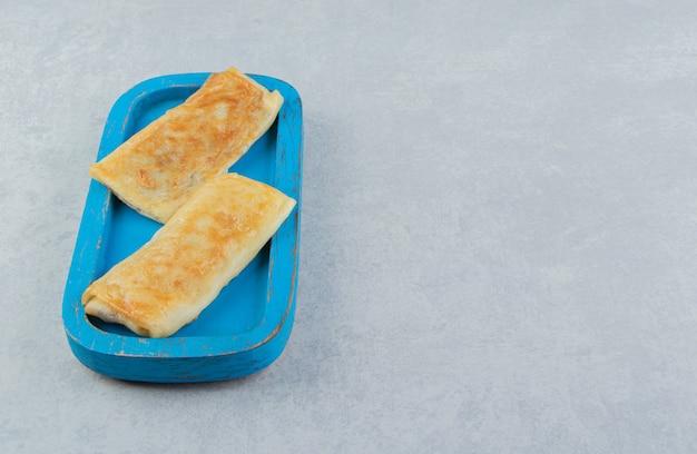 Panquecas recheadas com carne na placa azul.