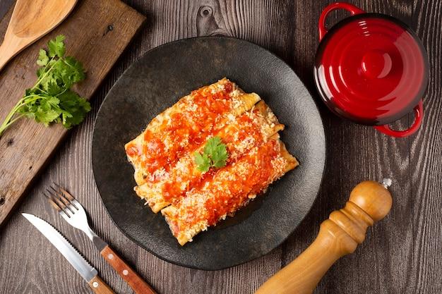 Panquecas recheadas com carne picada e cobertas com molho de tomate e queijo ralado.