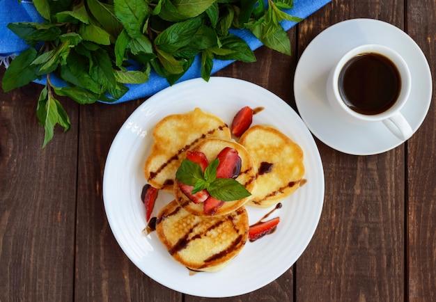 Panquecas rústicas com morangos frescos e chocolate em um prato branco e uma xícara de café