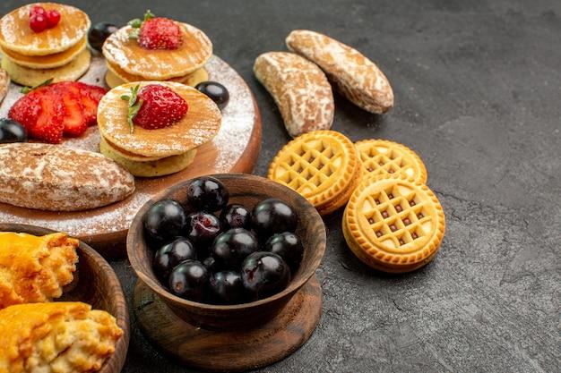 Panquecas saborosas de frente com doces diferentes em sobremesa de bolo de açúcar de mesa escura