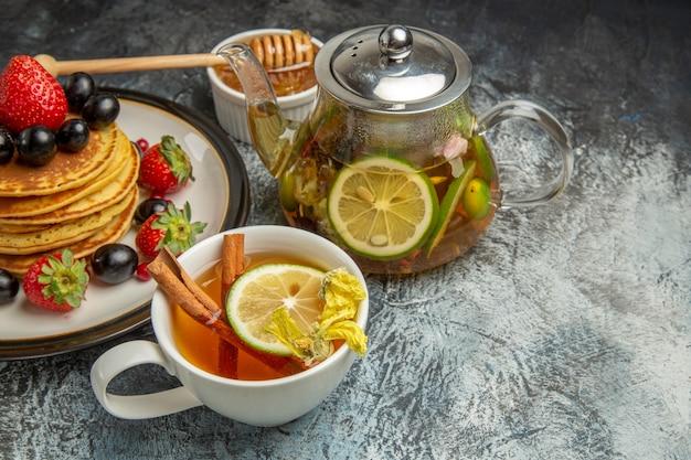 Panquecas saborosas de frente com frutas frescas no café da manhã com frutas frescas