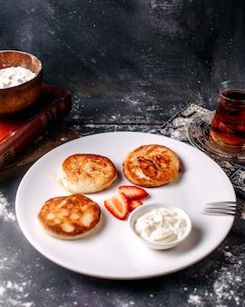 Panquecas saborosas de vista frontal, juntamente com chá quente com creme de leite e fatia de morango no backgorund brilhante