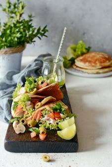 Panquecas sem açúcar com peru, alface, tomate, cogumelos em conserva, azeitonas e verduras em uma placa de madeira.