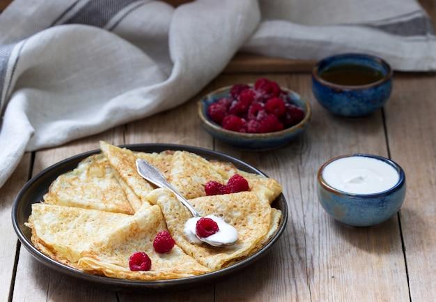 Panquecas servidas com creme de leite, framboesas e mel. o prato tradicional no carnaval e maslenitsa.