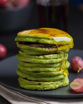 Panquecas verdes com chá matcha ou espinafre, mel e uvas vermelhas. ideias e receitas para um café da manhã saudável com ingredientes de superalimentos.