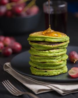 Panquecas verdes com chá matcha ou espinafre, mel temperado e uvas vermelhas.
