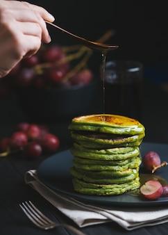 Panquecas verdes com chá matcha ou espinafre, mel temperado e uvas vermelhas