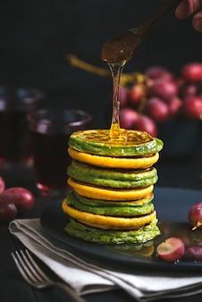 Panquecas verdes e amarelas com chá matcha ou espinafre, farinha de milho e cúrcuma, mel temperado.