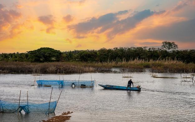 Pântanos rurais e pescadores dirigindo barcos ao pôr do sol