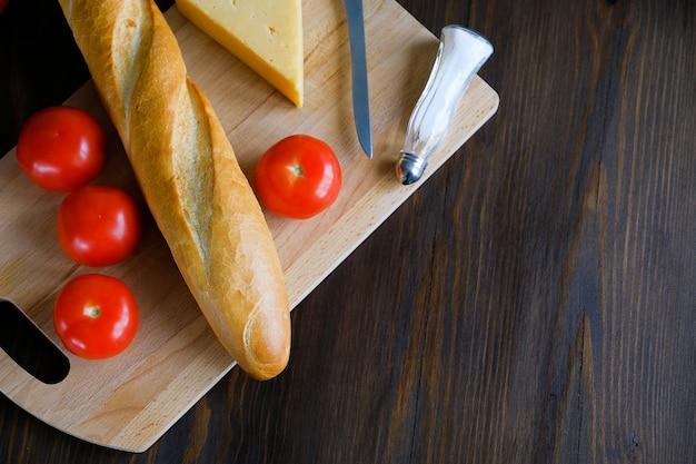 Pão acabado de cozer, tomate, queijo em uma mesa de madeira. produtos agrícolas orgânicos.