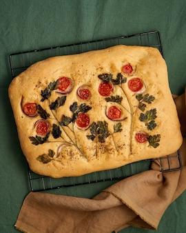Pão achatado com comida e arte focaccia com tomates em uma toalha de mesa de linho verde escuro