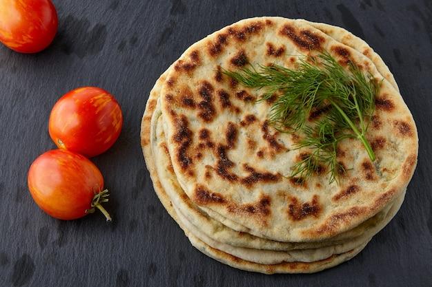 Pão achatado com queijo e ervas em um prato branco com tomates lanche vegetariano