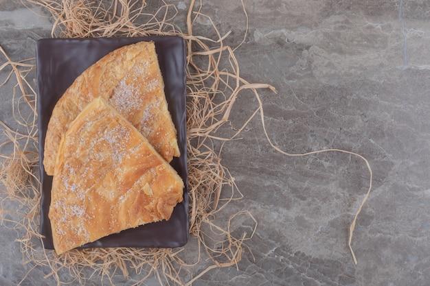 Pão achatado em flocos em uma pilha de palha em mármore