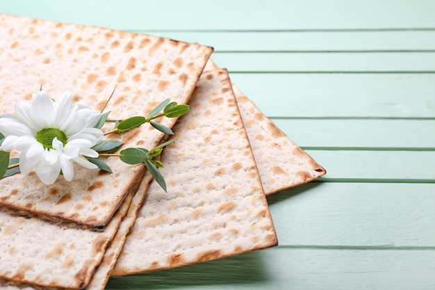 Pão achatado judaico para a páscoa e flores em fundo de madeira, closeup