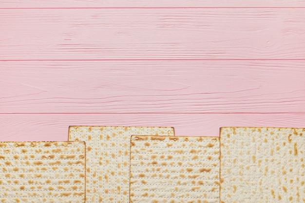 Pão achatado judaico para a páscoa em fundo de madeira
