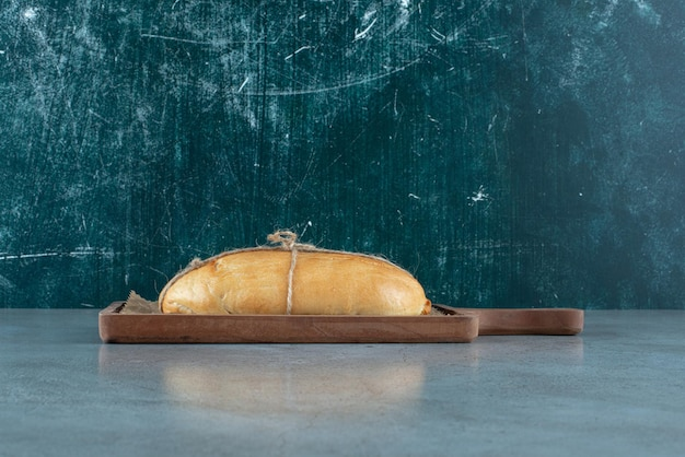 Pão amarrado com corda na placa de madeira.