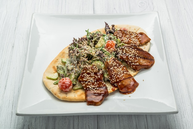 Pão árabe com carne e salada de legumes no prato