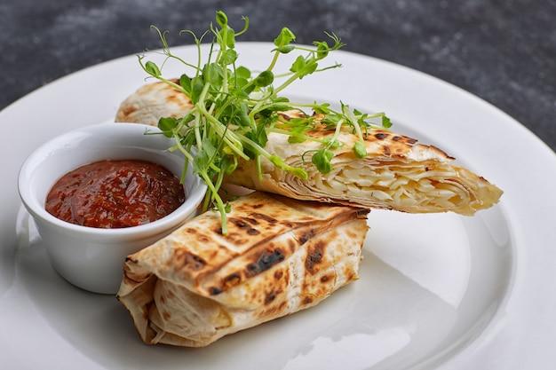 Pão árabe com queijo suluguni, molho, microgreen, em um prato branco, em concreto escuro.