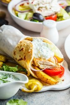 Pão árabe do giroscópio da galinha com vegetais e molho do tzatziki, fim acima, vertical. conceito de cozinha tradicional grega.