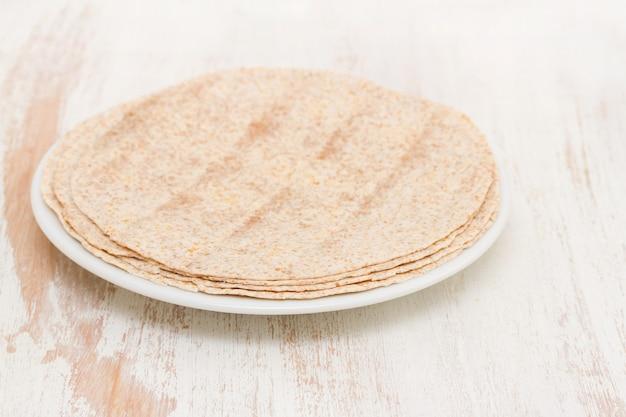 Pão árabe na chapa branca na superfície de madeira