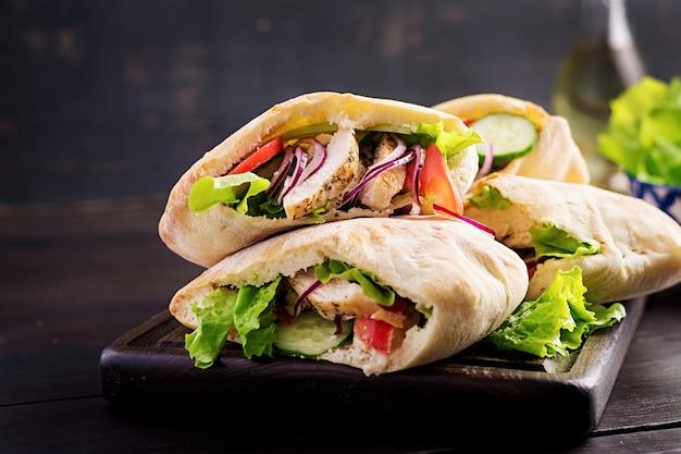 Pão árabe recheado com frango, tomate e alface em madeira, cozinha do oriente médio.